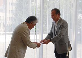 馬渕SIA会長(左)から寄付金の目録を受ける鈴木会長