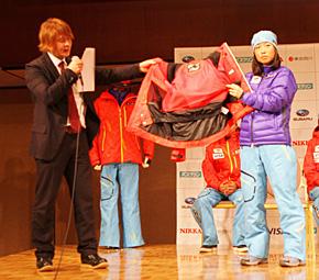 長年、フェニックスの競技ウェアを着用するクロスカントリーの石田正子選手をモデルのニューユニフォームを説明する佐藤課長(左)