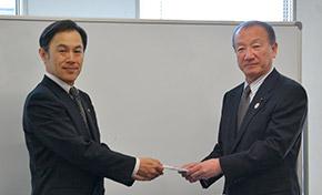 越田執行役員から鈴木会長へ寄付金が贈呈された