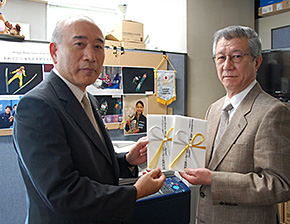 上冶ミズノスポーツ振興財団副会長(左)から助成金の目録が谷総務本部長に手渡された