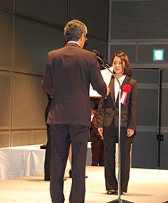緊張の表情で竹田会長から表彰を受ける髙梨選手